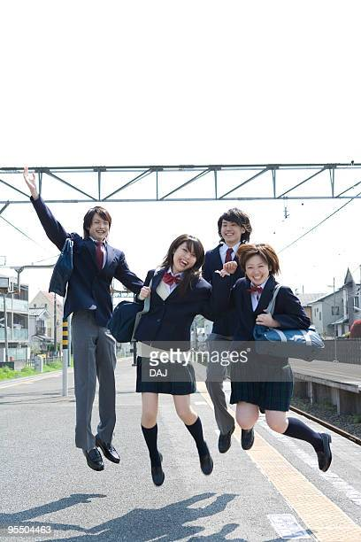 portrait of high school students jumping at platform, smiling - ユニフォーム ストックフォトと画像