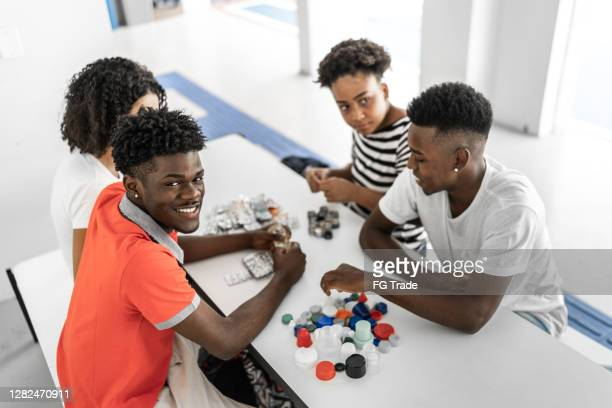 portrait of high school / university students separating recycling waste - students' union stock pictures, royalty-free photos & images