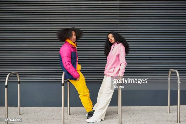 portrait of hip friends leaning against railings - street style stock pictures, royalty-free photos & images