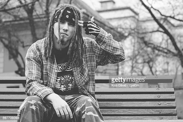 Portrait Of Hipster Aiming Temple While Sitting On Bench