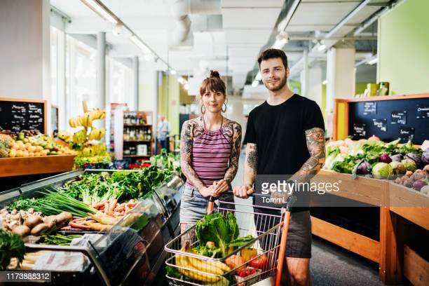 portrait of hipster couple shopping for groceries at local supermarket - produce aisle stock pictures, royalty-free photos & images