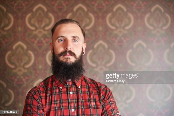 portrait of hipster in his front room - vollbart stock-fotos und bilder