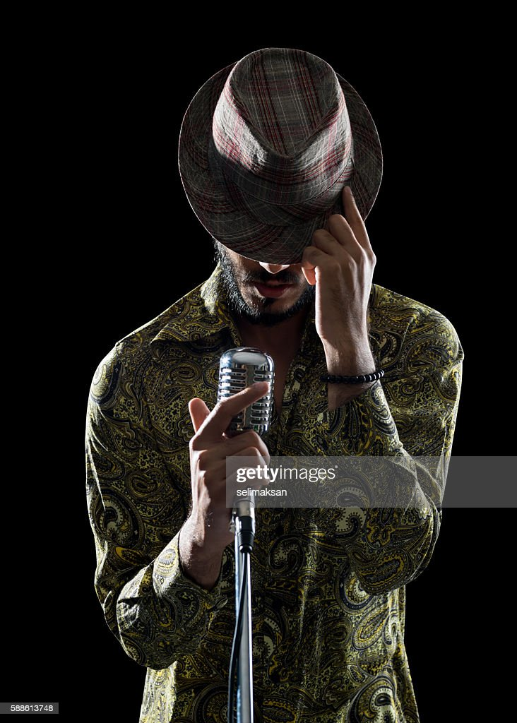 Portrait Of Hipster Man Singing While Touching His Hat : Stock Photo