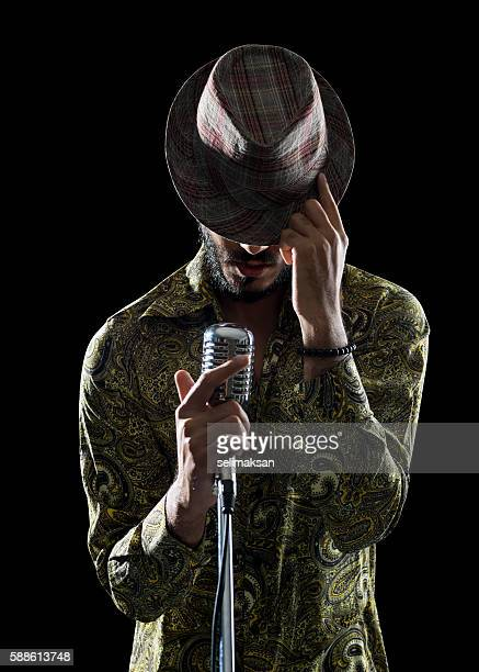 portrait of hipster man singing while touching his hat - rock object fotografías e imágenes de stock