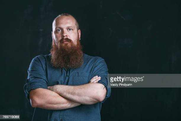 Portrait of hipster standing with arms crossed against black background