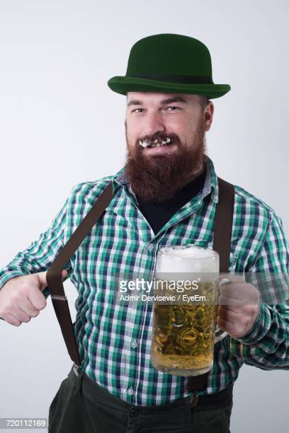 Portrait Of Hipster With Beer Glass Standing Against Gray Background