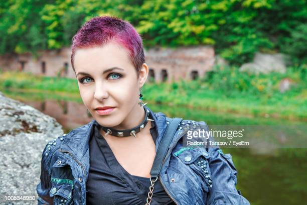 portrait of hipster woman against lake - female body piercing stock photos and pictures