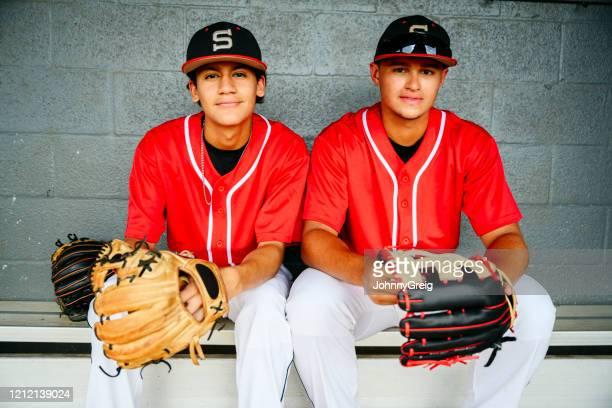 ダッグアウトで手袋を持つヒスパニック野球選手の肖像画 - スポーツユニフォーム ストックフォトと画像