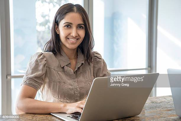 Portrait of Hispanic businesswoman using laptop and smiling