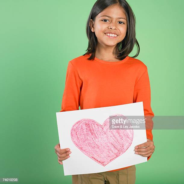 Portrait of Hispanic girl holding heart drawing