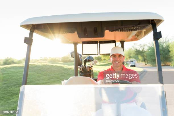 Portrait of Hispanic golfer driving golf cart