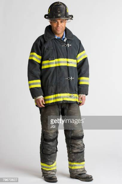 portrait of hispanic male firefighter - firefighter's helmet stock photos and pictures