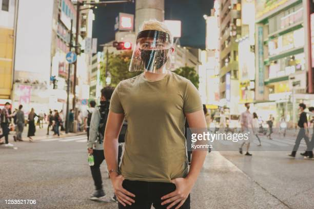 portrait of hispanic man wearing protective face mask and medical face shield - kyonntra stock pictures, royalty-free photos & images