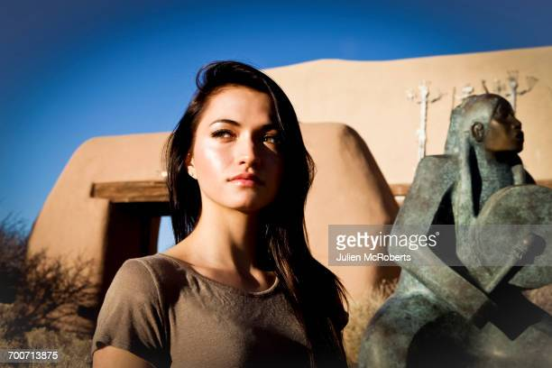 Portrait of Hispanic teenage girl near statue