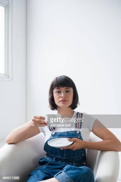 Portrait of Hispanic woman drinking coffee in armchair
