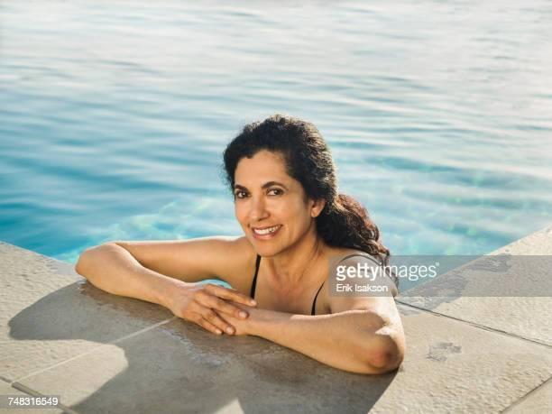 portrait of hispanic woman relaxing in swimming pool - paardenstaart haar naar achteren stockfoto's en -beelden