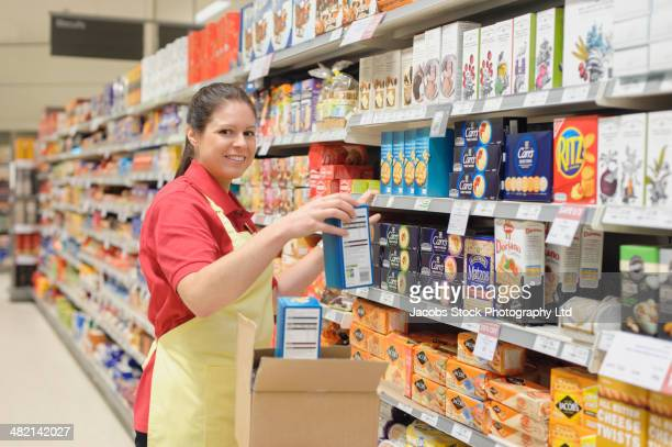 portrait of hispanic worker stocking shelves in supermarket - stacking stock pictures, royalty-free photos & images