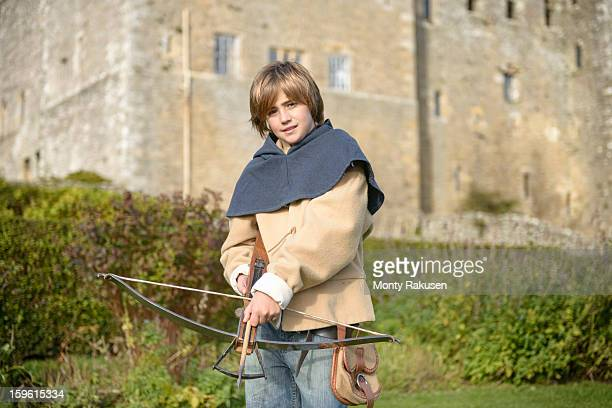 Portrait of history student in period dress with crossbow outside Bolton Castle, a 14th century Grade 1 listed building, Scheduled Ancient Monument