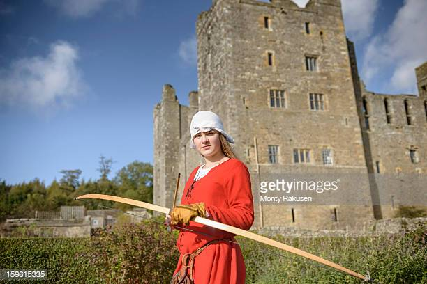 Portrait of history student in period dress with longbow outside Bolton Castle, a 14th century Grade 1 listed building, Scheduled Ancient Monument