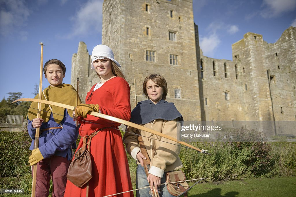 Portrait of history students in period dress with longbows and crossbow outside Bolton Castle, a 14th century Grade 1 listed building, Scheduled Ancient Monument : Stock Photo