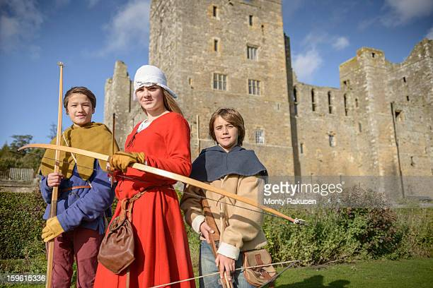 Portrait of history students in period dress with longbows and crossbow outside Bolton Castle, a 14th century Grade 1 listed building, Scheduled Ancient Monument