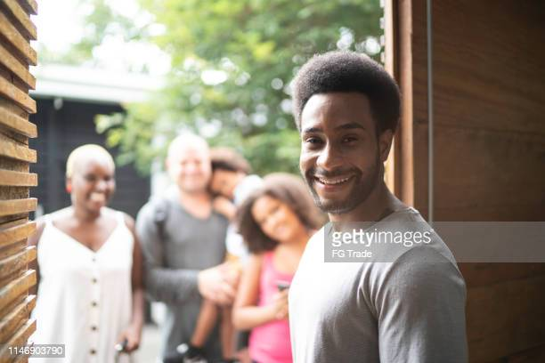 portrait of home owner welcoming family to rental house during vacation - sharing economy stock pictures, royalty-free photos & images