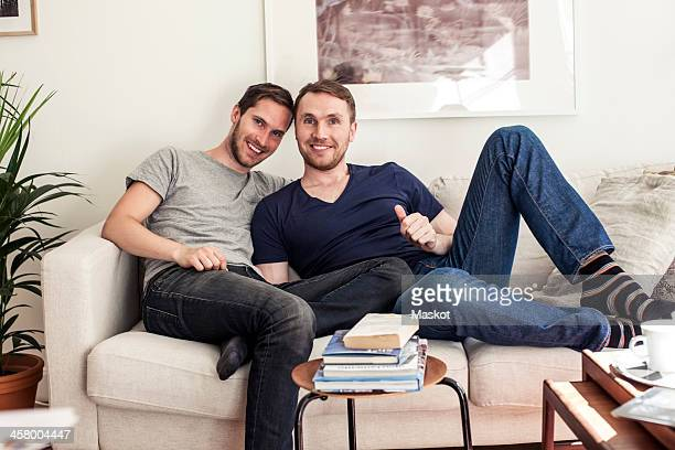 Portrait of homosexual couple sitting together on sofa at home