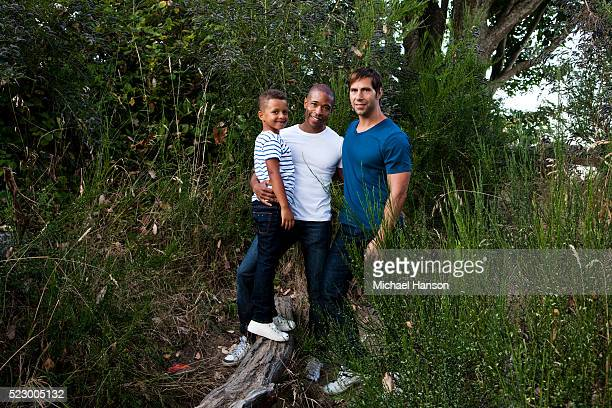 Portrait of homosexual, multiracial couple in a field with their son (7-9)