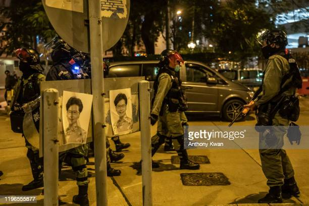 Portrait of Hong Kong Chief Executive Carrie Lam are seen on a road sign pole as riot police secure an area during a demonstration in Fanling...