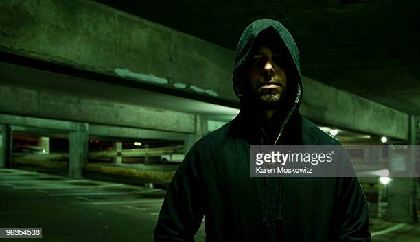 portrait of hooded man in empty parking garage - criminal stock pictures, royalty-free photos & images