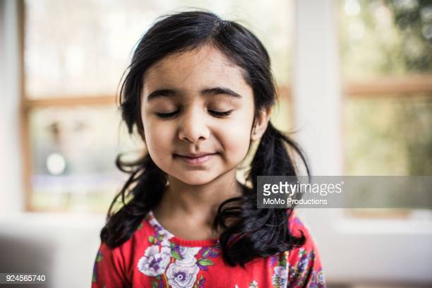 portrait of hopeful young girl at home - eyes closed stock pictures, royalty-free photos & images
