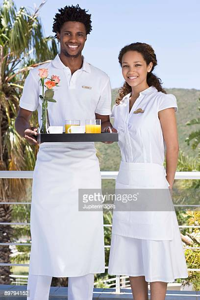 Portrait of hotel room attendants with breakfast room service tray