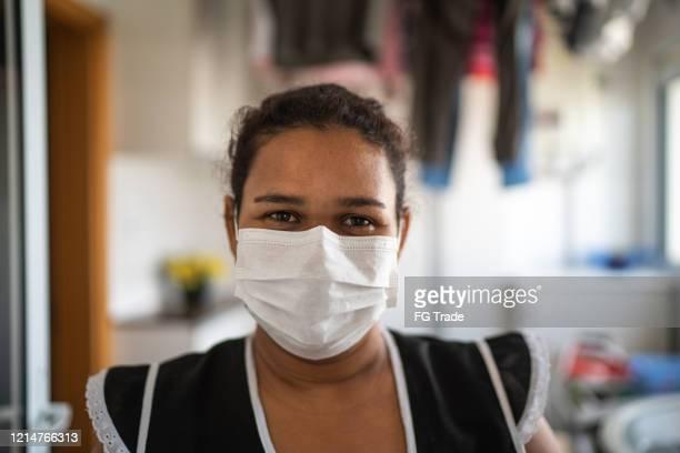 portret van huishoudster die beschermend masker bij huis draagt - latijns amerikaanse en hispanic etniciteiten stockfoto's en -beelden