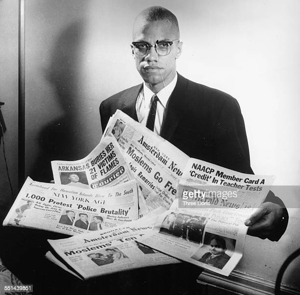 Portrait of human rights activist Malcolm X reading stories about himself in a pile of newspapers circa 1963