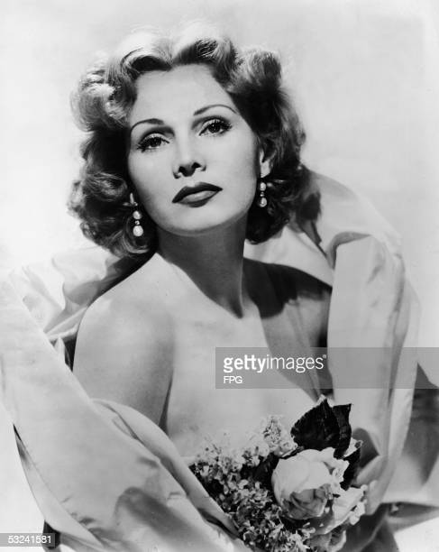 Portrait of Hungarian actress Zsa Zsa Gabor wearing a stole and carrying a bouquet of flowers 1950s