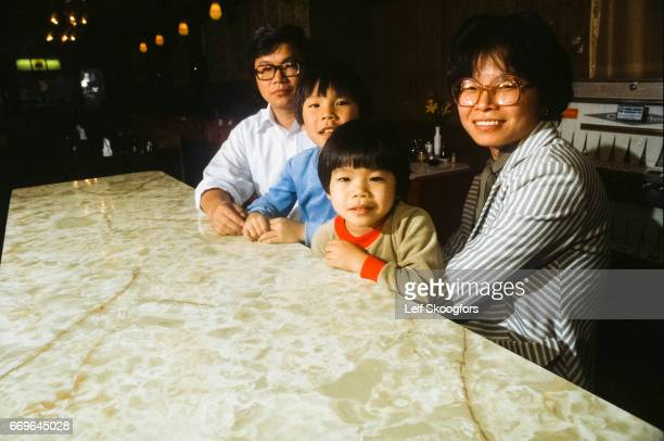 Portrait of husband and wife buisness owners and their children as they sit together at a tabletop in their South Philadelphianeighborhood Vietnamese...