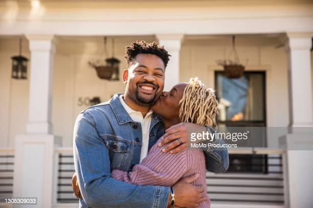 portrait of husband and wife embracing in front of home - love stock pictures, royalty-free photos & images