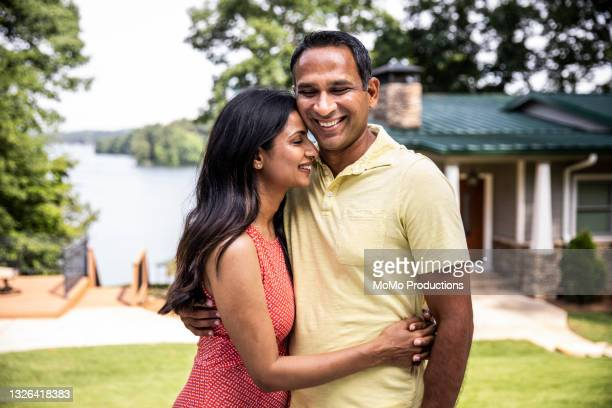portrait of husband and wife in front of lake home - sleeveless dress stock pictures, royalty-free photos & images