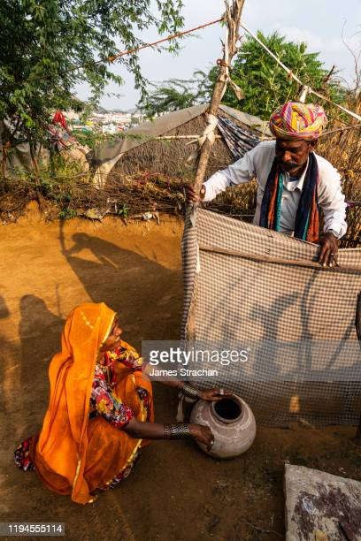 portrait of husband and wife rajasthanis talking in their yard at dusk by their bathroom, pushkar, rajasthan, india (two model releases) - james strachan stock pictures, royalty-free photos & images