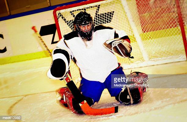 Portrait of ice hockey player kneeling on ice in front of goal, tilt