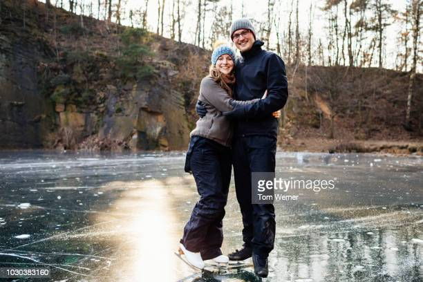 portrait of ice skating couple embracing - casal heterossexual imagens e fotografias de stock
