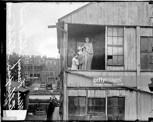 Portrait of Ida McClelland Stout an African American sculptor standing on a tenement porch next to a monumental Ethiopian sculpture Chicago Illinois...
