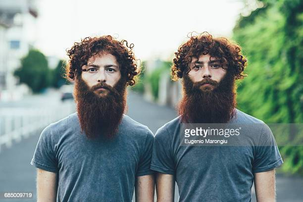 Portrait of identical adult male twins with red hair and beards on sidewalk