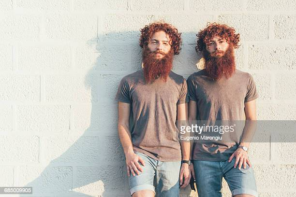 Portrait of identical adult male twins with red hair and beards against wall