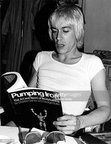 Portrait of Iggy Pop reading 'Pumping Iron' magazine in Arturo Vega's apartment in the East Village, New York, 1976.