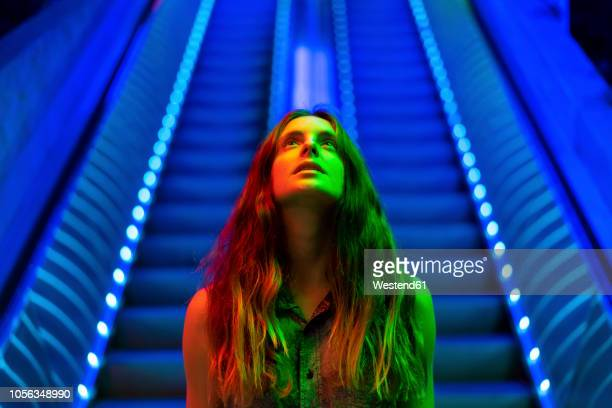 portrait of illuminated young woman in front of blue lighted escalator looking up - regarder en l'air photos et images de collection