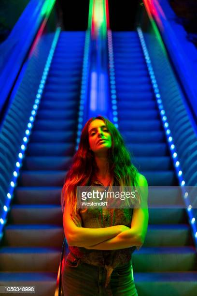 portrait of illuminated young woman in front of blue lighted escalator - arrogance stock pictures, royalty-free photos & images