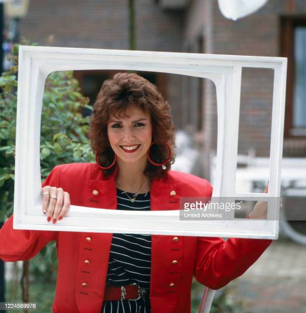 Portrait of Ilona SchulzBaumgart the wife of the singer Klaus Baumgart posing with a television frame Germany 1979