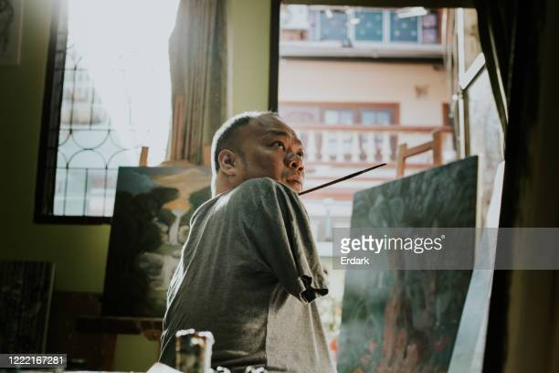 portrait of independent disable thai artist man while working at home - artist stock pictures, royalty-free photos & images