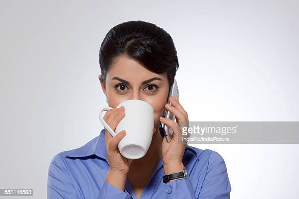 Portrait of Indian businesswoman drinking coffee while answering phone against gray background